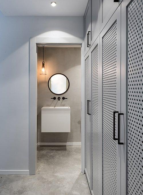 ארון שירות עם מסגרת עץ ורשת מפח מחורר מסתיר את מכונת הכביסה והמייבש. פתח לכביסה מתוך חדר הרחצה מוביל היישר לתוך הארון | צילום: עמית גושר