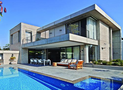 בית פרטי שנבנה ביישוב במרכז הארץ, המשלב בטון מודרני עם בריקים כפריים ויוצר הרמוניה בין סוגים שונים של חומרים