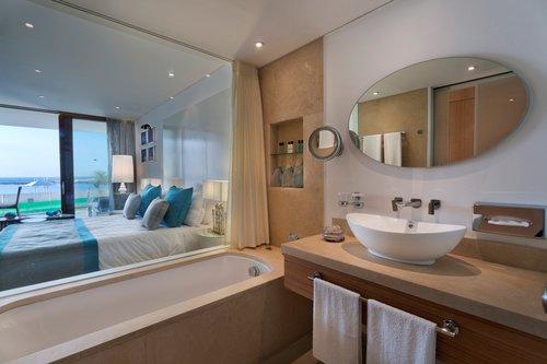 חדר אמבטיה מחופה אבן טבעית שמופרד מהחדר המרכזי באמצעות חלון זכוכית,סוויטה במלון נחשולים   צילום: אסף פינצ'וק