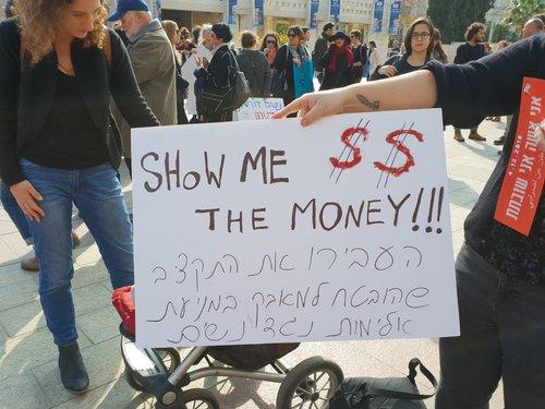 שלט שקורא להעביר את התקציב המובטח למניעת אלימות נגד נשים בהפגנה בכיכר ספרא בירושלים | צילום: פייני סוקניק
